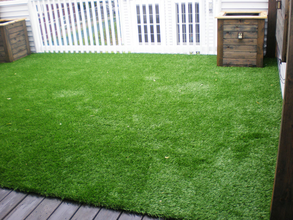Long synthetic grass in small New Jersey lawn with white fences