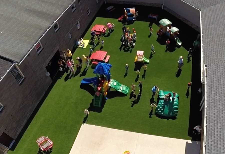 Aerial view of busy outdoor day care play area with playground turf