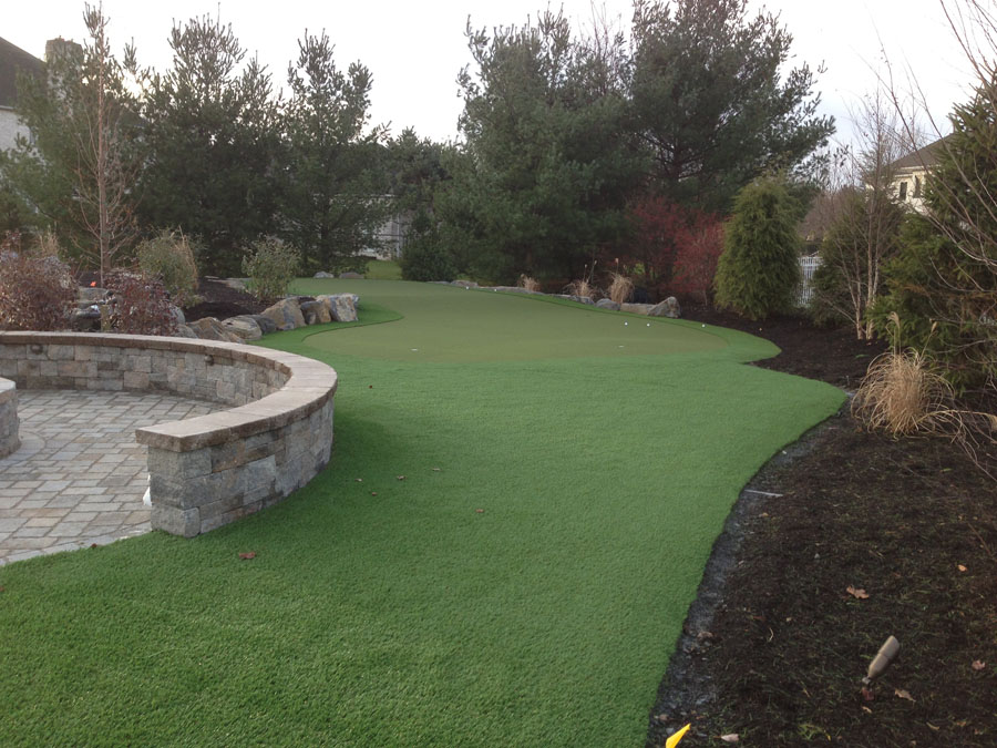 Easton artificial turf lawn with practice green and stone patio