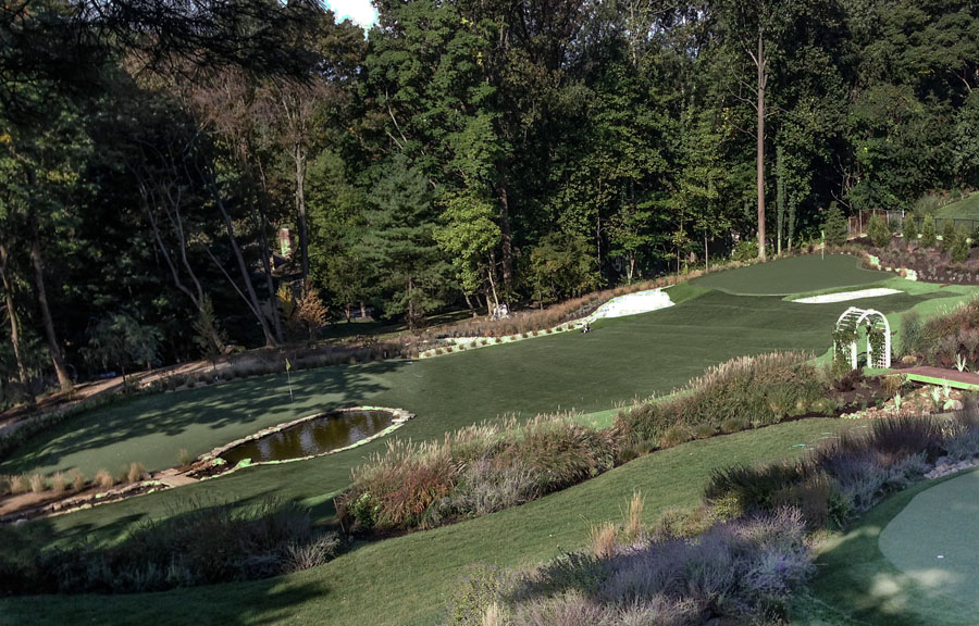 Large backyard in Harrisburg with putting green backed by forest