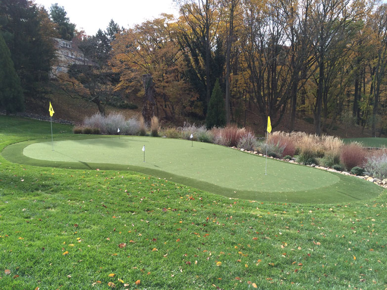 Putting green install with a slight hill and fall forest foliage