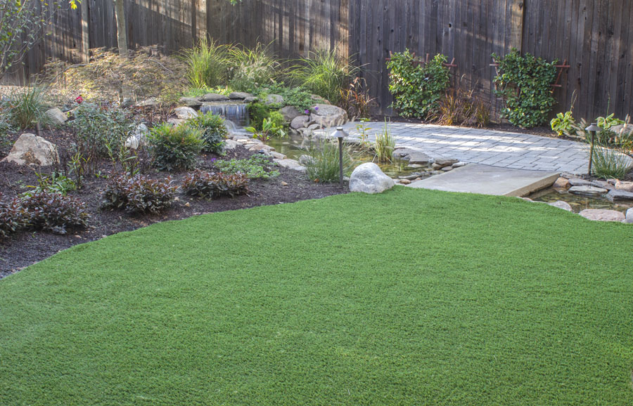 Small artificial lawn installation surrounded by low plants and pavers