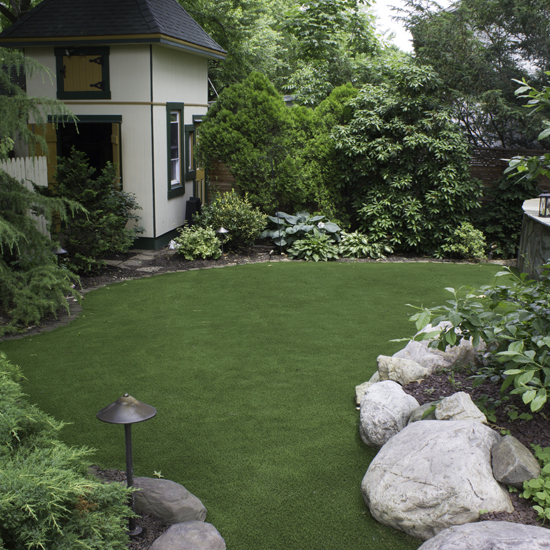 Trees surrounding a secluded artificial turf backyard in PA