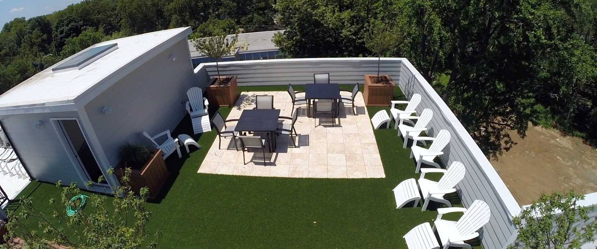 Roof top with an artificial turf patio lined with lounge chairs