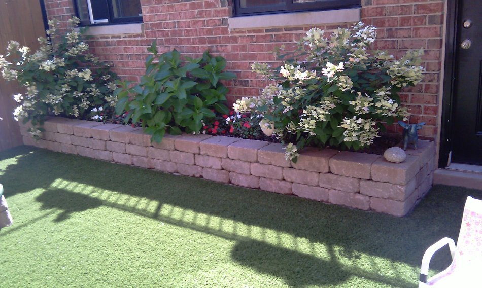 Augustine backyard grass with flower bed and brick exterior