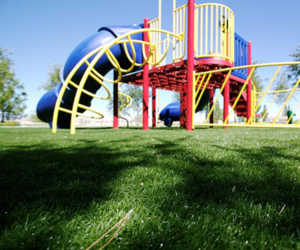 Close-up of artificial playground grass under NJ playset