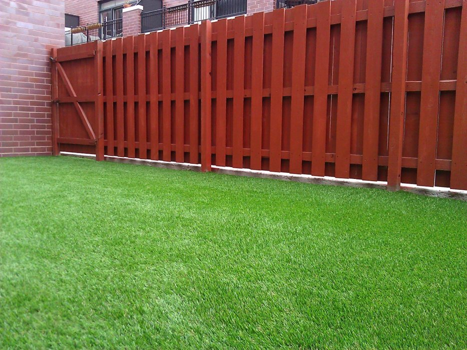Red fence lining an artificial grass lawn in New Jersey