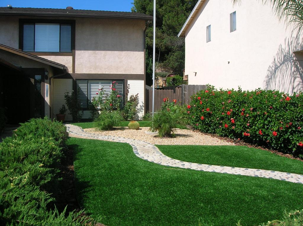 Stone pathway going through a synthetic grass backyard
