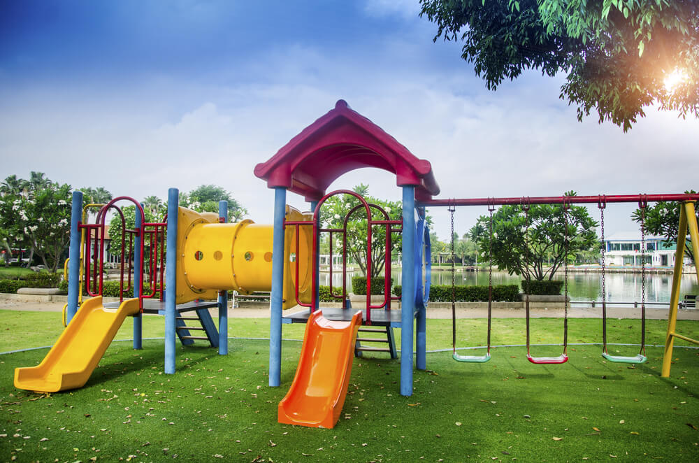Artificial turf playground surface underneath outdoor play equipment at New Jersey daycare facility