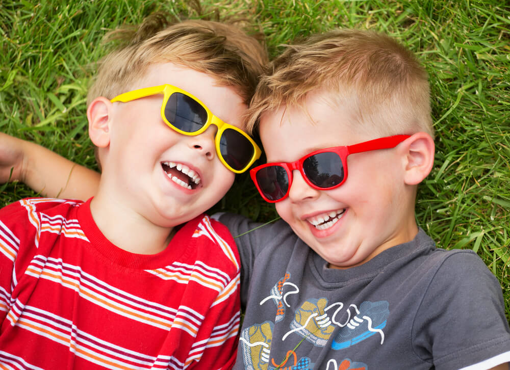 Two toddler boys with colorful sunglasses on laugh on top of artificial turf in New Jersey